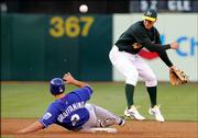 The Oakland Athletics' Mark Ellis, right, forces out the Kansas City Royals' Tony Graffanino at second base while turning a double play. The Royals won, 8-7, Tuesday in Oakland.