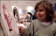 Nicole Spencer, then 3, paints during preschool at the Lawrence Arts Center in this March 2005 file photo. Decorating professional Deborah Wiener says if parents display children's creations smartly, they may never have to buy artwork or posters again.