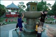 Children play in the South Park fountain during a recent Lawrence City Band concert.