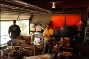 Auctioneer Doug Riat, center, and Aubrey Gilbert, move through the crowded garage of Gilbert's deceased grandmother Willie Stagg Thursday afternoon, as they prepare for a two-day auction this weekend in which the family will sell many of Stagg's possessions including her many collectibles. Among other things, according to Riat, Stagg carried a collection of over 200 Barbie Dolls, 2000 albums and 5000 miniature stuffed animals.