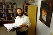 Rabbi Zalman Tiechtel, reads some of the many jewish books on hand at Chabad a international outreach and education center to promote Judaism at 1201W. 19th.