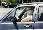 An unidentified driver pulls in to traffic while using a cell phone in Lawrence, Kan., Friday, June 2, 2006. City officials in this college town are proposing the most aggressive cell phone ban in the country. The proposal would ban the use of hald-held and hands-free cell phones by drivers.
