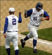Kansas coach Ritch Price gives his son Ryne Price a high-five after Ryne hit a home run in the seventh inning against Hawaii, Friday, June 2, 2006, in an NCAA tournament regional baseball game in Corvallis, Ore. Kansas won 9-6.