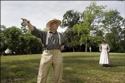In clothing reminiscent of that worn in the mid-1800s, Jeff Quigley points to what was thought to be a blackjack oak tree during a tour of the Black Jack Battlefield. The battle occurred June 2, 1856. The anniversary was celebrated Saturday at the site. Quigley's wife, Kathy, is pictured at right.