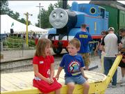 Ally and Aaron Mcgee, of Garnett, wait for their parents, Rochelle and Craig, to take their picture Saturday in front of Thomas the Tank Engine at the Midland Railway in Baldwin after the family rode the train. Saturday was the second of the six-day event this summer to help raise money for the Midland Railway Historical Assn.