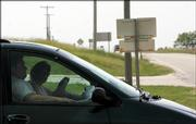 A driver looks for traffic before crossing U.S. Highway 59 at Baldwin Junction, the intersection with U.S. Highway 56.  Residents are concerned that signage, like that above, is blocking the view of drivers at the notoriously dangerous intersection.