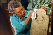 Martha Parker, Clinton Lake Museum  curator, works on the gravestone of a young black girl found near Kanwaka Corner. Parker and others have planned several events promoting a new museum.