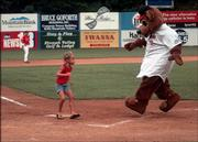 Ted E. Tourist, mascot for the Class A South Atlantic League Asheville Tourist minor-league baseball team, loses a race around the bases to Sarah Tucker in this July 11, 2002, file photo taken at McCormick Field in Asheville, N.C.