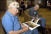 Cal Tempelton, left, and Webb Kohl, both Rangers in town for the three-day World War II reunion at the Lawrence Holidome, sign last year's group pictures for a friend.