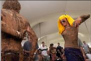 Clarence Mills, right, and Mike O'Neill, both from Colorado, are caked in mud as they dance inside the Revival Tent to the music of Shanti Groove. Large crowds gathered Sunday for the final day of the Wakarusa festival at Clinton Lake.