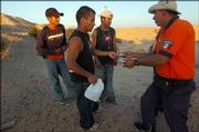 Carlos Estrada, a police agent working with the Mexican government's migrant assistance unit, Grupo Beta, distributes packets of rehydration powder to a group of migrants last week in the desert near San Luis Rio Colorado, Mexico. Left to right are Porfiro Vera Jimenez, 19, Cesar Garcia Vazquez, 23, and Hugo Sanchez Martinez, 19.