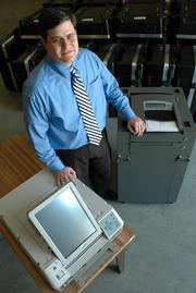 Jamie Shew, Douglas County clerk, displays the two styles of new computerized voting machines. Eighty of each machine will be tested and ready to put into use for the Aug. 1 elections.