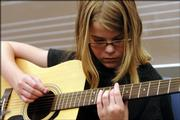 Pam Curn, 11, of Overland Park, picks some strings as she tunes her guitar Wednesday at Band Camp in Kansas University's Murphy Hall. More than 500 campers will participate in programs through July 14.