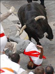 A runner falls after being hooked by a bull's horn during a San Fermin bull run in Pamplona, Spain, in 2004.