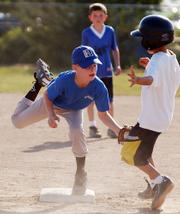 Rookie Baseball player Aric Trent of the Flame Hawks tags out Jets player Hunter Sharp during a game on Wednesday at the Youth Sports Inc.