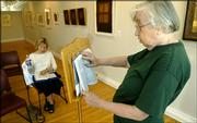Lawrence resident Eleanor Symons, right, leads a reading through the book of Exodus as Barbara Wasson follows along during a Bible reading Monday afternoon at Signs of Life, the art gallery and bookstore at 722 Mass. Signs of Life is sponsoring the reading, which began at 7 a.m. Monday and will continue through Saturday until the entire Bible has been read.