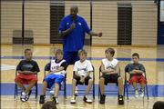 Danny Manning, Kansas University's director of student/athlete development, back, speaks to participants during Bill Self's basketball camp. Manning singled out campers, from left, Tyus Bricso, Trenton Morris, Nick Gochenour, Dylan Queen and Trevor Rine, as examples of an unselfish team during his talk Monday at Horejsi Center.