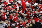 The Carolina Hurricanes celebrate with the Stanley Cup after defeating the Edmonton Oilers, 3-1, in Game 7 of the Stanley Cup finals. The Hurricanes won the Cup with Monday night's victory in Raleigh, N.C.
