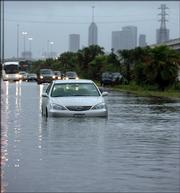 A stalled vehicle sits in high water along Interstate 45 in Houston. Torrential downpours created a nightmare commute for Houston-area residents on Monday, flooding some major traffic arteries.
