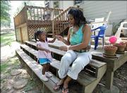 Anita Britten, right, plays with her niece Amber Britten, 3, at her home in Lithonia, Ga. As more hybrid adjustable rate mortgages, or ARMs, adjust upward and housing prices begin to dip, many Americans can't refinance out of the this riskier type of loan and face the risk of foreclosure.