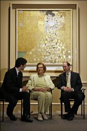 "Maria Altmann, center, chats with Michael Govan, left, director of the Los Angeles County Museum of Art, and her attorney E. Randol Schoenberg in front of a Gustav Klimt painting of Altmann&squot;s aunt titled ""Adele Bloch-Bauer I,"" at the Los Angeles County Museum of Art in this April 4 file photo. The painting, looted from Altmann&squot;s family in 1938 by the Nazis, was sold to the Neue Galerie in New York for a record-setting amount."