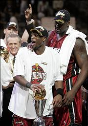 As center Shaquille O'Neal, right, and head coach Pat Riley, background, look on, Miami guard Dwayne Wade holds his MVP trophy after the Heat clinched their first NBA title. Miami secured the championship with a 95-92 victory over Dallas in Game 6 of the NBA Finals on Tuesday night.