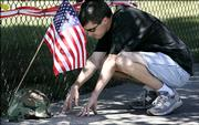 """Lorn Dunten, 31, pauses at a shrine for U.S. Army Pfc. Thomas Lowell Tucker in Madras, Ore. U.S. forces on Tuesday recovered the bodies of two American soldiers reported captured by insurgents last week, Tucker and Pfc. Kristian Menchaca, 23, of Houston. An Iraqi defense ministry official said the men were tortured and """"killed in a barbaric way."""""""