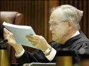 Justice Robert Davis holds a school finance report while asking questions of the state's attorneys during arguments before the Kansas Supreme Court Thursday in Topeka.