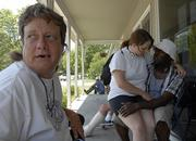 """Sitting on the front porch of the Lawrence Community Shelter are, from left, Rosemary Hubbard, Josie Miller and Jimmie Bowser. The shelter has an interest in purchasing the former Lake View Manor property in southern Lawrence to replace its current site. Hubbard, who uses a wheelchair, and Miller and Bowser, who have all used the current shelter, think a move to the former Lake View Manor could be good. """"We&squot;d help fix it up,"""" Miller said at the shelter Friday."""