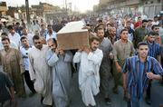 A funeral procession takes place Saturday in the Shiite slum of Sadr City, Iraq, for two men, Ahmed Abdullah and Jassim Mohammed. Both were killed Friday while marching to the Buratha mosque on the other side of the city to protest a suicide attack a week ago on the revered Shiite shrine there.