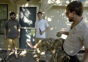 "Roommates Josh Davis, left, and Adam Stuart, center, hang out with Stuart's brother Ian outside Josh and Adam's house. Adam is faced with the threat of being prosecuted for having a ""disorderly house"" as defined in a city ordinance."