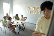 Sanae Eda, assistant professor of East Asian Languages at Kansas University, gives instruction on proper calligraphy techniques to a class of home-schooled children Wednesday near 15th and Wakarusa Streets. Eda plans to offer a free course to the public, tentatively scheduled for late July.