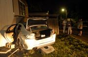 Bystanders wait around the scene of a crash in which a car was reportedly forced off the road and into a mobile home around 10:30 p.m. Monday evening in the Gaslight Village mobile home park on West 31st Street. The owner of the mobile home was not home at the time of the crash.