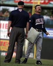 Asheville Tourists manager Joe Mikulik, at right in photo, walks away with second base in the fifth inning after being ejected during game against the Lexington Legends.