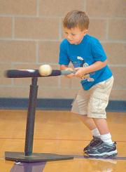 Louden Schwab hits the ball during a game of Blastball on June 19 at the East Lawrence Center. In Blastball one player hits the ball and runs to jump on a single base while other players try to catch the ball.