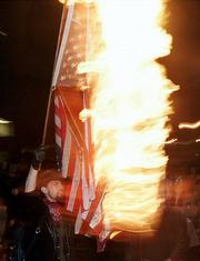 A protester burns an American flag to protest President Bush's second inauguration during a march in Portland, Ore., in this Jan. 20, 2005, file photo. A measure to ban flag desecration has only a slight chance of passing the Senate this week, analysts believe.