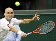 Andre Agassi returns a shot from Andreas Seppi. Agassi won the second-round match, 6-4, 7-6 (2), 6-4, on Thursday at Wimbledon, England.