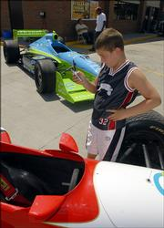 John Herriott, 8, of Basehor, snaps a photo of an Indy Racing League race car parked at Casey&#39;s General Store in Basehor. Representatives from the ethanol industry, Kansas Speedway and the IRL converged at the convenience store Thursday to promote ethanol-enriched fuel.
