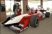 Indy Racing League's Vitor Meira, left, touches the tread of an Indy car parked at Casey's General Store in Basehor. Panther Racings' Meira spoke about the benefits of ethanol at a news conference Thursday in Basehor. Next year, the IRL will use 100 percent ethanol fuel.