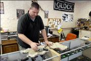 Jeffery Howlett, owner of Kansas Firearms Specialties in Tonganoxie, cleans off a handgun Thursday in his store. A new law, which takes effect Saturday, prohibits weapons in businesses that post signs stating that guns aren't allowed.