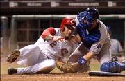 The Cincinnati Reds' Felipe Lopez is tagged out at home plate by Kansas City Royals catcher Paul Bako during the eighth inning of their game at Great American Ball Park in Cincinnati. The Reds pulled out a 6-5 victory Thursday.