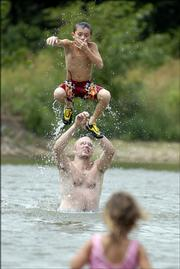 Robert Buck launches his son, Alex, 11, into the air in the Clinton Lake swimming area. The Buck family, from Bonner Springs, came to Clinton Lake on Friday to relax. Temperatures hovered around the century mark on Friday and are expected to remain hot and humid until the Fourth of July.