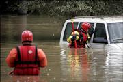 Members of the New York-Task Force 2 disaster response team wade through fast-moving water Friday as they search a car in Conklin, N.Y. The high water prevented many residents from being able to visit their homes.