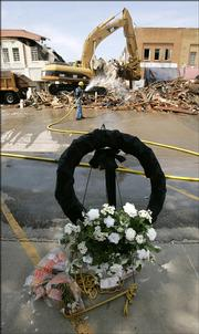 A wreath stands as a  memorial to Tony Komer as demolition continued Friday of the Clinton Elks Club building in downtown Clinton, Mo. Komer, who was the leader of the club, died when the building collapsed Monday.