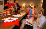 Anthony Van Schmus, 9, foreground, reads a book as a craft session begins in the Lawrence Public Library's gallery. Despite a nationwide technological movement, visits to the local library have increased 31 percent between 2000 and 2005.
