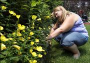 """Trisha Leu, 17, who has lost 60 pounds since undergoing gastric band surgery in March, weeds the garden in the front yard of her Wheeling, Ill., home. The American Medical Assn. is considering a proposal to label children in the highest weight category as """"obese"""" instead of the current term, """"overweight."""" Trisha says she dislikes the term obese because she thinks """"it sounds mean. It doesn&squot;t sound good."""""""