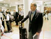 "Mark Erickson, vice president of continuing education at the Culinary Institute of America, waits to board Delta Flight 656 for Newark at Hartsfield Jackson Atlanta International Airport. Erickson, of Marietta, Ga., is a super-elite frequent flier who travels 200,000 miles a year. He looks for perks such as first-class upgrades or being able to board first instead of getting free airplane tickets for his frequent business. ""The last thing I want to do is travel (more),"" he says."