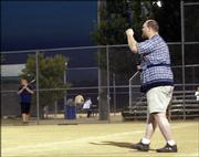 Jon Wagler pumps his fist after one of his softball teammates blasts a double at Clinton Lake Sports Complex. Wagler has been relegated to coaching third base after dislocating his shoulder more than three weeks ago.