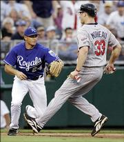 Royals third baseman Mark Teahen prepares to tag out Minnesota's Justin Morneau. Morneau had reached base on a double but was thrown out on a fielder's choice by Angel Berroa on Wednesday in Kansas City, Mo.