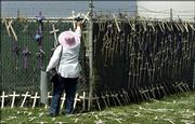 Emily Miriam Gallegos puts crosses on a fence outside a Border Patrol station near San Diego. The crosses symbolize migrants who died attempting to cross the border into the United States. A Republican-led House panel held a hearing on immigration Wednesday at the station.